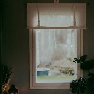 White linen roll up curtain hanging in window.