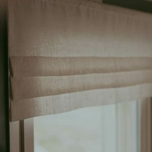 Linen faux roman curtain valance hanging in a window.