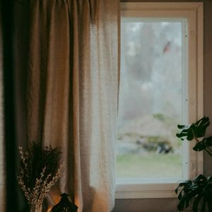 Ecological white Linen curtains hanging in cozy window.