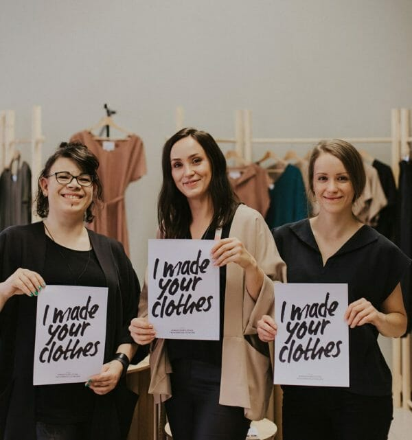three seamstresses from RESTYLE sewing atelier in Vaasa Finland is holding up signs for Fashion revolution campaign 'I made your clothes'.