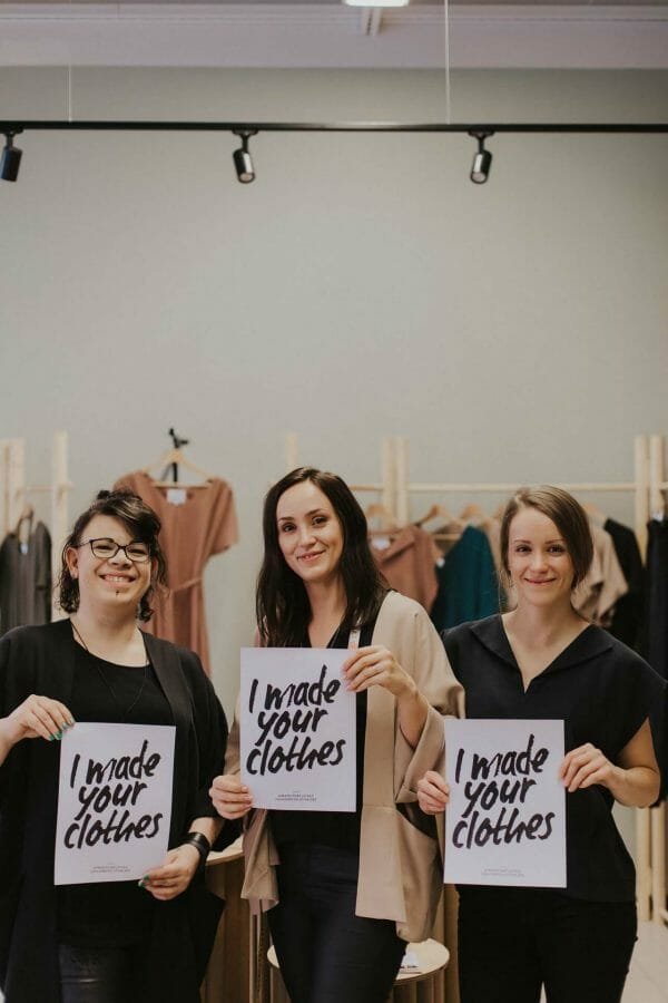 sewing atelier restyle by mia vaasa crew is holding up fashion revolution posters.