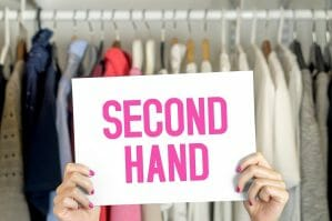 woman holding up sign with text 'second hand' in her wardrobe.